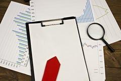Carpeta con una hoja en blanco, los gráficos y la lupa, oficina roja del lazo imagen de archivo