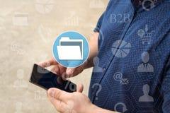 Carpeta de archivos, DMS en la pantalla táctil con un fondo de la falta de definición del hombre de negocios con el teléfono El c fotos de archivo