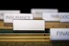Carpeta de fichero con la escritura de la etiqueta en blanco en cabinete de archivo Fotos de archivo libres de regalías