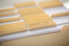 Carpetas amarillas con las etiquetas y el papel en fila fotografía de archivo