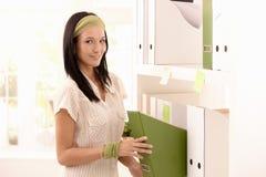Carpetas atractivas del embalaje de la mujer en estante Fotografía de archivo libre de regalías