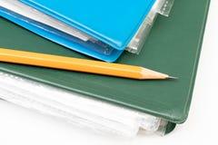Carpetas coloridas cosechadas con los documentos y las cuentas y un l?piz amarillo en la tabla blanca imagen de archivo