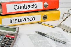 Carpetas con los contratos y el seguro de las etiquetas foto de archivo libre de regalías