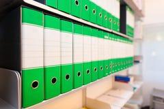 Carpetas con los documentos en estantes de la oficina Imágenes de archivo libres de regalías