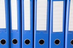 Carpetas de la oficina aisladas Fila de las carpetas azules de la oficina con las etiquetas en blanco en el escritorio Ficheros y imagen de archivo libre de regalías