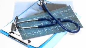 Carpetas médicas y estetoscopio que dan vuelta contra blanco