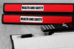 Carpetas rojas con la salud y la seguridad escritas en la etiqueta en un escritorio fotos de archivo libres de regalías