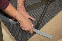 Carpeting a staircase. Craftsman carpeting a staircase with vintage tools Stock Photo