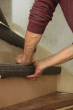 Carpeting a staircase. Craftsman carpeting a staircase with vintage tools Stock Photos