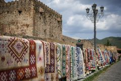 Carpets with handmade ornaments hang on the streets of the Georgian city for sale. stock photography