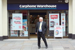 Carphone Warehouse. London, England - Sept 11th, 2014: A man in a suit waits in front of a Carphone Warehouse store in Central London. The UK company was founded Stock Images