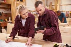Carpinteiro With Apprentice Looking em planos na oficina Fotografia de Stock