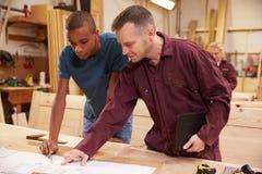 Carpinteiro With Apprentice Looking em planos na oficina Imagens de Stock Royalty Free