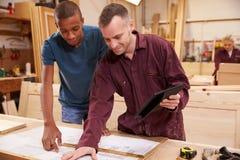 Carpinteiro With Apprentice Looking em planos na oficina Imagens de Stock