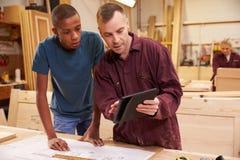 Carpinteiro With Apprentice Looking em planos na oficina Fotografia de Stock Royalty Free
