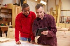 Carpinteiro With Apprentice Looking em planos na oficina Foto de Stock Royalty Free