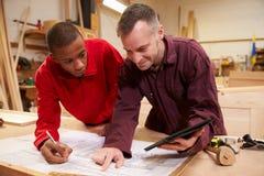 Carpinteiro With Apprentice Looking em planos na oficina Imagem de Stock Royalty Free