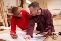 Carpinteiro With Apprentice Looking em planos na oficina Fotos de Stock Royalty Free