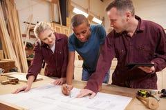 Carpinteiro With Apprentices Looking em planos na oficina Imagem de Stock Royalty Free