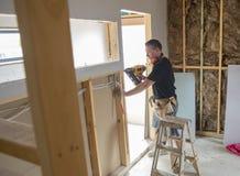 Carpinteiro atrativo e seguro do construtor ou madeira de trabalho do homem do construtor com broca elétrica no canteiro de obras imagem de stock