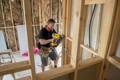 Carpinteiro atrativo e seguro do construtor ou madeira de trabalho do homem do construtor com broca elétrica no canteiro de obras