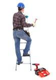 Carpinteiro com o martelo na escada portátil Foto de Stock Royalty Free