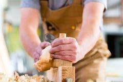 Carpinteiro com plaina e o workpiece de madeira na carpintaria