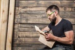 Carpinteiro com uma barba que senta-se em um forro do banco imagens de stock royalty free