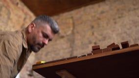 Carpinteiro criativo que verifica o material de madeira para ver se h? mais ulterior transforma? filme