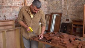 Carpinteiro criativo que verifica o material de madeira para ver se h? mais ulterior transforma??o filme