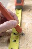 Carpinteiro da mulher que toma a medida Imagem de Stock