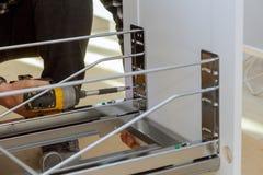 Carpinteiro de montagem da mobília que parafusa usando um escaninho de lixo sem corda das gavetas da chave de fenda na cozinha imagens de stock royalty free