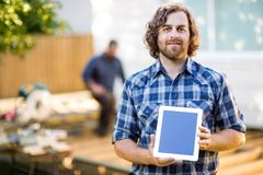 Carpinteiro Displaying Tablet Computer com colega de trabalho fotos de stock royalty free