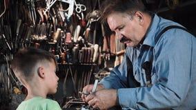 Carpinteiro do vovô com seu neto na oficina Imagens de Stock Royalty Free