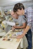 Carpinteiro e aprendiz que olham as amostras de madeira Fotografia de Stock Royalty Free