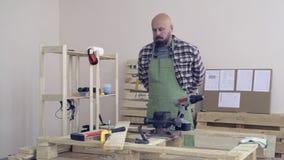 Carpinteiro em sua oficina Veste um avental verde, e rola suas luvas da camisa antes do trabalho video estoque