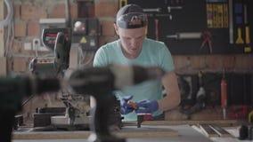 Carpinteiro especializado que corta uma parte de detalhe do cartão em sua oficina da carpintaria, usando uma serra circular com o video estoque