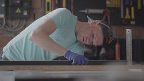 Carpinteiro especializado que faz as medidas da parte de detalhe do cartão em sua oficina da carpintaria, muitas ferramentas no video estoque