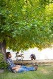 Carpinteiro With Eyes Closed que inclina-se no tronco de árvore fotos de stock royalty free
