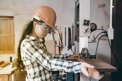 Carpinteiro fêmea asiático bonito que usa a máquina de lixar elétrica para a madeira foto de stock royalty free