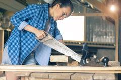Carpinteiro fêmea com um serrote, vendo as placas na oficina Fotografia de Stock