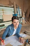 Carpinteiro fêmea Drawing On Blueprint na tabela Fotos de Stock