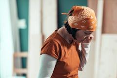 Carpinteiro fêmea durante a conversação de telefone celular séria com cliente imagens de stock royalty free