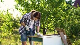 Carpinteiro fêmea na camisa verificada que corta a prancha de madeira com serra de vaivém elétrica vídeos de arquivo