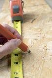 Carpinteiro fêmea que toma medidas Imagens de Stock