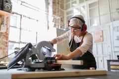 Carpinteiro fêmea superior que trabalha com uma serra circular Fotografia de Stock Royalty Free