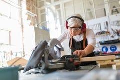 Carpinteiro fêmea superior que trabalha com uma serra circular Fotos de Stock