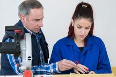 Carpinteiro With Female Apprentice que trabalha no terreno de construção fotografia de stock royalty free