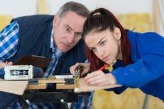 Carpinteiro With Female Apprentice que trabalha no terreno de construção fotos de stock