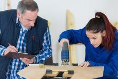 Carpinteiro With Female Apprentice que trabalha no terreno de construção fotografia de stock